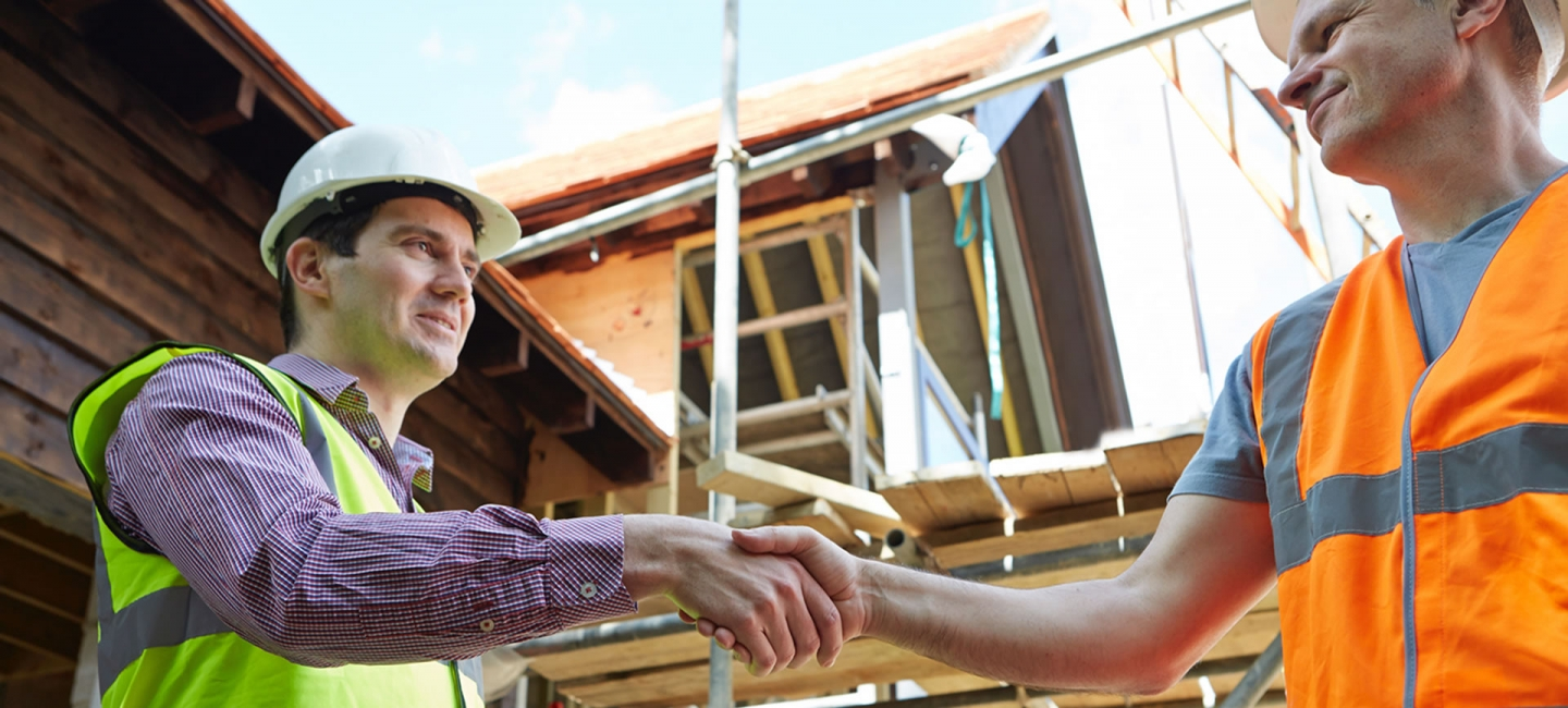 Two men shaking hands on building site